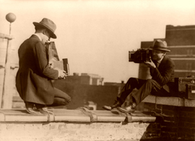 Two photographers taking each others picture with hand-held cameras while perched on a roof, between 1909 and 1932
