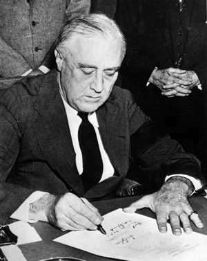 President Roosevelt signs declaration of war against Japan