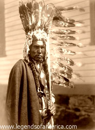 Blackfoot Piegan war-bonnet and coup-stick, Edward S. Curtis, 1910