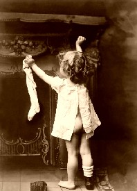 Child hangs a Christmas stocking in 1901