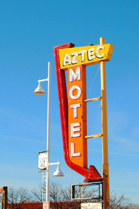 The Aztec Motel Sign still stands next to an empty lot.