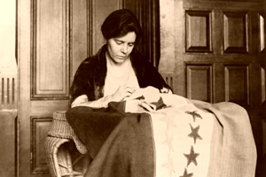 Alice Paul sewing the Suffrage Flag, about 1916.