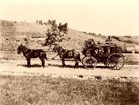 Stagecoach with guard sitting on top, protecting whatever wealth it might  have been carrying.