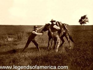 Saddling the bronc by Erwin E. smith, 1910