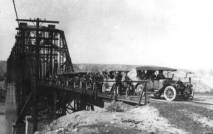 Model T's cross the planked railroad bridge