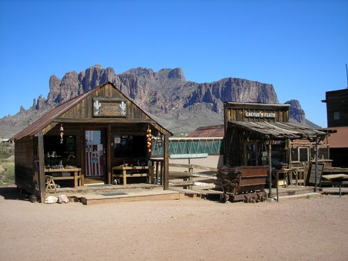 The superstition Mountains can be seen behind these  old buildings in nearby Goldfield, Arizona