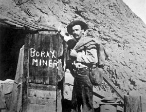 A Borax miner about to enter his home in an abandoned tunnel