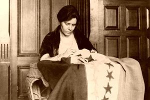 Alice Paul sewing Suffrage Flag about 1916