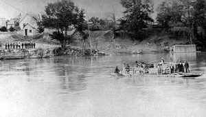 A Covered Wagon is ferried across a river