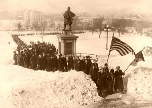 Mother Jones and 600 miners marching to the State Capitol at Denver, Colorado, to present their grievances to Governor Ammons regarding sending militia to the Southern Coal Fields. The Ludlow battle flag was carried at the head of the column.