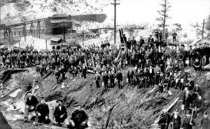 A large group of miners stand before the Castle Gate Mine in about 1900.