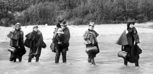 Actresses crossing the Dyea River in Alaska