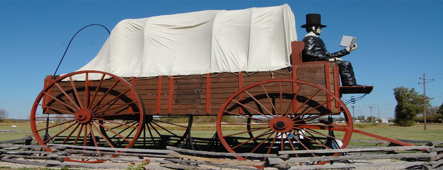 Abraham Lincoln sits in a covered wagon welcoming visitors to his namesake town, by Kathy Weiser-Alexander.
