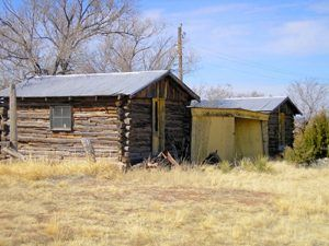 Log cabins in Ancho, New Mexico by Kathy Weiser-Alexander.