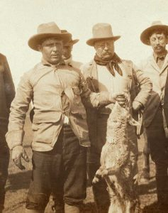 Jack Abernathy holding wolf standing next to President Theodore Roosevelt