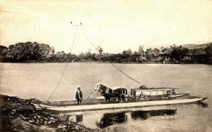 Wagon crossing a river on ferry.